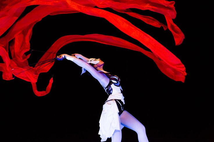 Dancer in white costume with red ribbon in black light (UV). Crystal Light Show - Anta Agni.