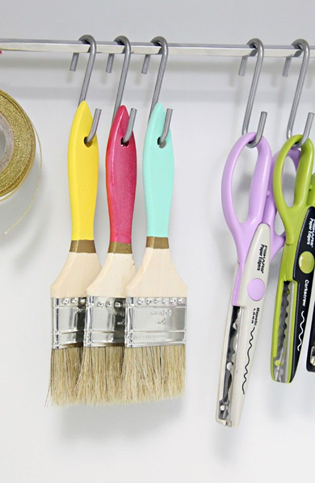 Instead of sticking your brush collection in a jar or mug, opt for hanging them on hooks like these.