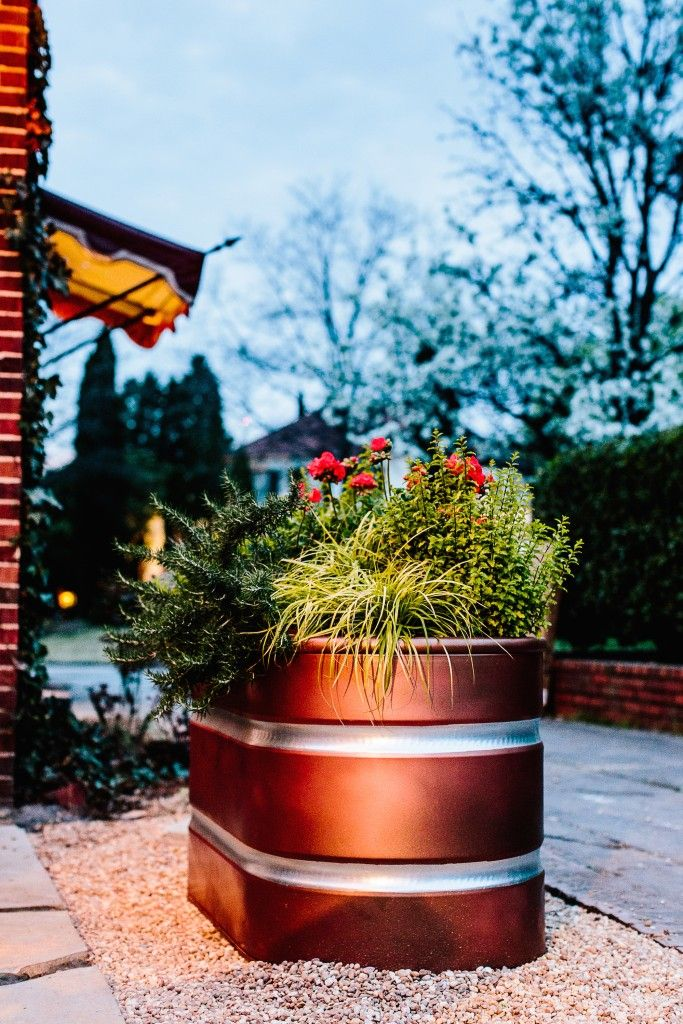 Galvanized stock tank painted to look like copper for plantings.