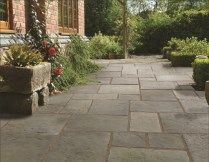 A lovely period style random pattern patio featuring Pavestone Tanners Mill Grey Green flagstone style concrete paving. #GreyPavingSlabs #ConcretePaving