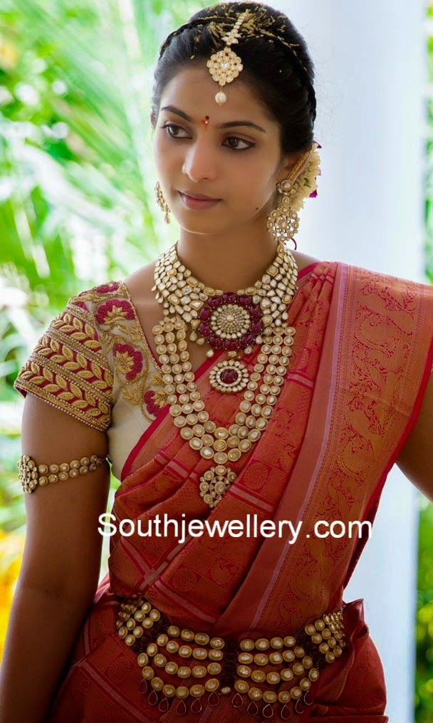Pretty bride Madhuri in kundan wedding jewellery set. She is adorning a rich kundan jadau choker studded with kundans and rubies; a medium length kundan haram studded with three rows of kundans; Kundan vaddanam, kundan armlet, kundan tikka and kundan earrings.