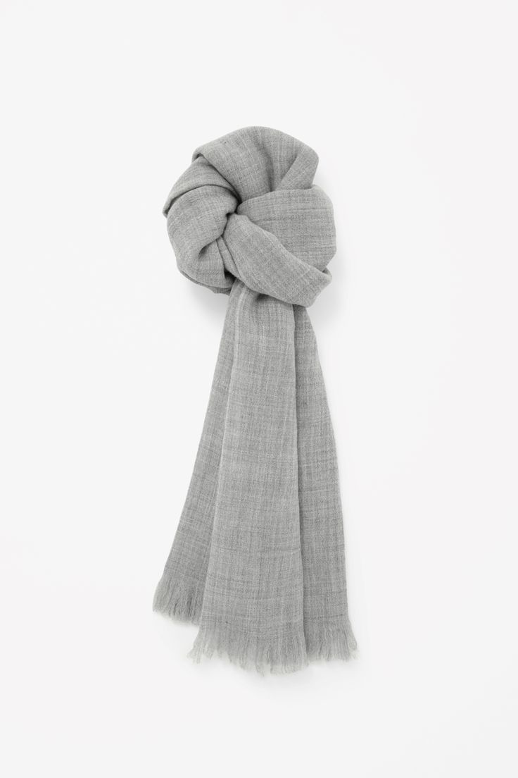 Made from finely woven wool with a subtle melange quality, this large rectangle scarf has softly frayed edges.