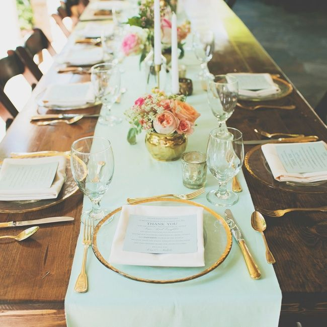 Long farm tables lined with mint table runners and gold silverware greeted guests at the reception site.