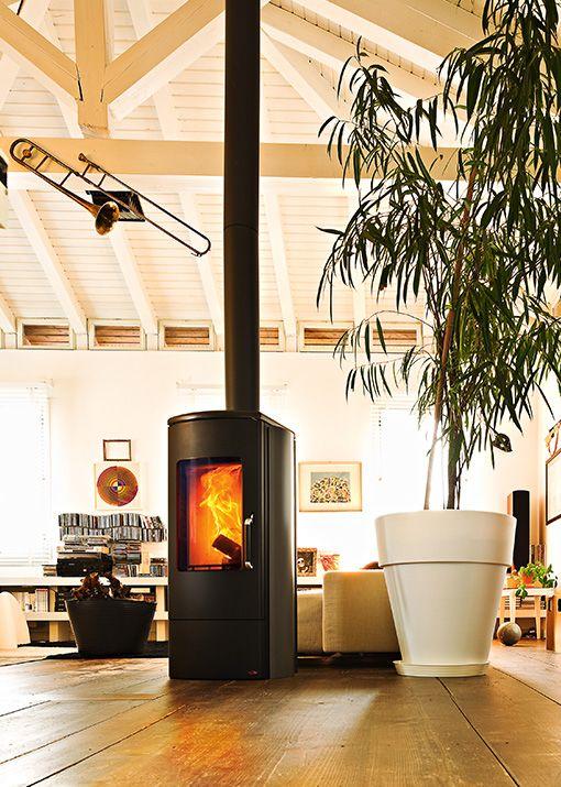 Heizofen mit lackierter Stahlstruktur. Der Rahmen und das Glas der Tür sind gerundet. Feuerstelle aus Alutec®, Brennebene aus Gusseisen und Holzscheithalterung aus Stahl.