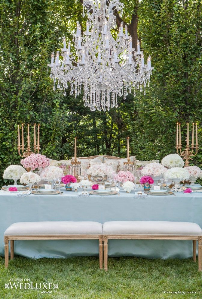 gorgeous vintage french inspired tablescape with hedge background and crystal chandelier