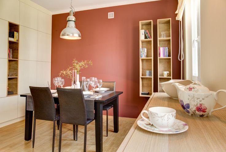 Aranżacja jadalni z centralnie ustawionym stołem i kompletem krzeseł. Wokół system szafek zabudowujących ścianę oraz pojemne komody, które są niezbędne do przechowywania serwisu stołowego.