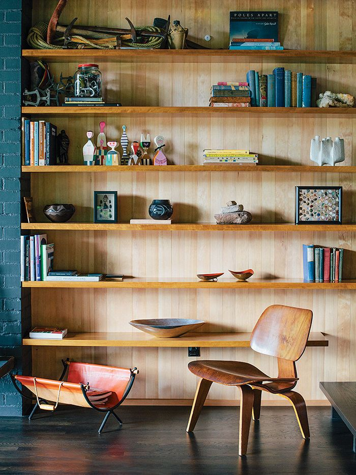 Molded Plywood Lounge Chair by Charles and Ray Eames for Herman Miller sits in front of built-in shelving in untreated hemlock.