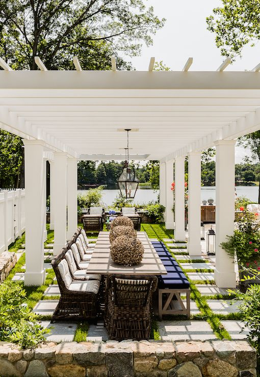 Amazing dining pergola is dotted with carriage lanterns illuminating a long wood dining table lined with wicker dining chairs on one side and a long wood bench topped with navy cushion on the other side.