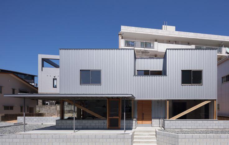 美容室、カフェ、webデザインオフィスが内包された店舗併用住宅である。 関門海峡を渡った本プロジェクトは、クライアントが地元で活躍するデザイナー集団であり、彼らの地域に対する熱い想いによって実現された。そこへ創造される建築には地域のデザインアイコンとしての役割が求められた。 木造2階建ての1階には、美容師(ご主人)とカフェオーナー(奥様)のご夫婦、webスタッフ数名が営む合計3店舗が最小限のスペースへそれぞれ入り組むように配置され、2階はご夫婦の住まいが併設されている。 極端に抑えられた建設コストに対し、前面道路から1m程の敷地高低差を処理する擁壁材(型枠コンクリートブロック)、木造軸組在来工法による建物四隅への壁量材(筋交い)らに建築デザインの要素を見出し、シンプルかつダイナミックな空間を構成している。 西側の大庇は西日対策のほか、住宅アプローチやカフェテラスとして機能し、単調なファサードにアクセントを与えている。 (松本 健志)
