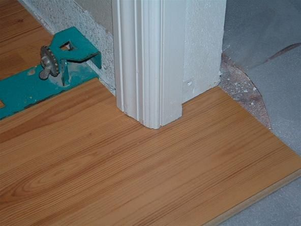 Under cutting door jambs with a hand saw, before installing laminate flooring