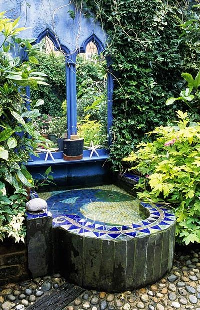 Ann Frith patio garen with colorful mosaic water feature and trompe l'oeil mirrors