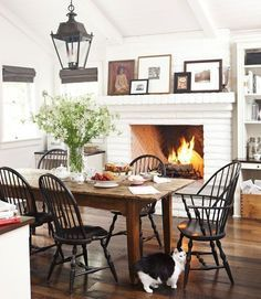 Cozy Farmhouse Dining Room, wood table, black chairs, lantern light, fireplace, framed pictures