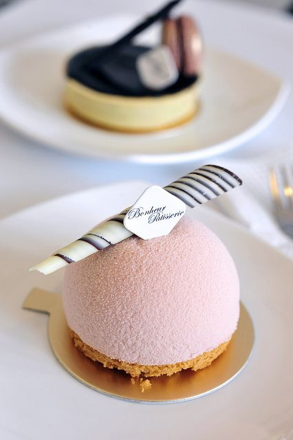 A domed light peach mousse with a sakura infused chocolat blanc centre, resting on a piece of butter pound, with a pâte sablée disc as a base.