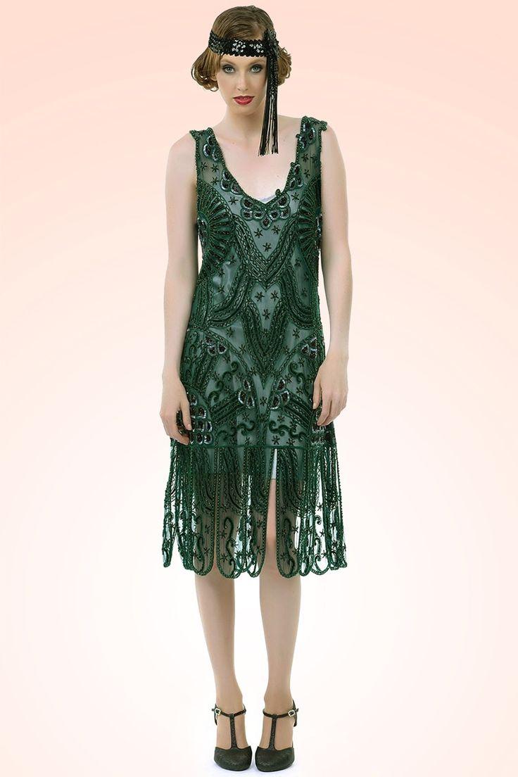 Wat een schoonheid deze20s Royal Flapper Dress in Emerald GreenvanUnique Vintage! Deze opvallende partyjurk is een geweldige handgemaakte reproductie van de elegante flapper dresses van de jaren 20!  Prachtig loose-fit model met een elegante diepe V-hals aan voor- en achterzijde die prachtig bewerkt is. De jurk is geheel versierd met minuscule zwarte en groene glimmende kraaltjes en reflecterende pailletten die er met de hand opgestikt zijn, trés chique! De rok...