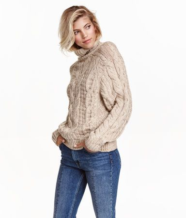 Light beige melange. Long-sleeved turtleneck sweater in a soft cable knit with wool content.