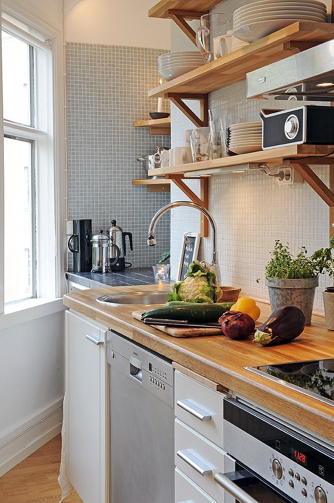 A warm inviting kitchen. glass mosaic splashback - organic feel. wooden shelves and wooden benchtop add warmth.