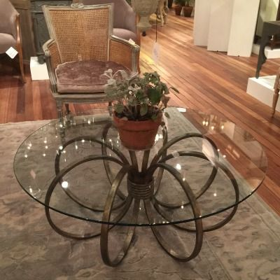 The Penthouse Coffee Table features an intricately swirled wrought iron base design that supports a glass top - made by Currey & Co.