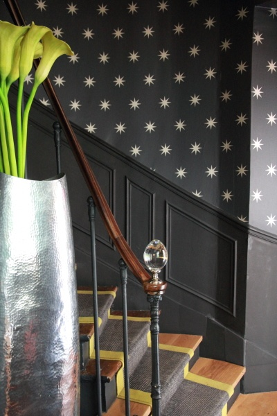 Black wall with metallic stars, black panelling below, natural wood stairs with grey and gold runner and black risers and lilies in a silver vase make for magical hallway decor.