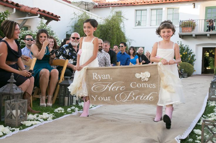 If you have a few adorable kids in your family, chances are you've already selected your flower girl and ring bearer. But if youhavea bevy of little ones you'd like to include in your ceremony, it can be tough to figure out what roles they can each play. Older kids may enjoy handing out programs or serving as junior bridesmaids and groomsmen, but these types of jobs may be overwhelming for the younger set. A charming alternative is to ask one or two kidsto carry a han...