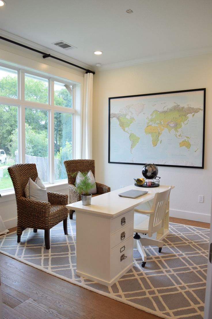 Home office with large window, world map wall decor, wicker chairs, Pottery Barn Bedford desk and geometric wool rug.