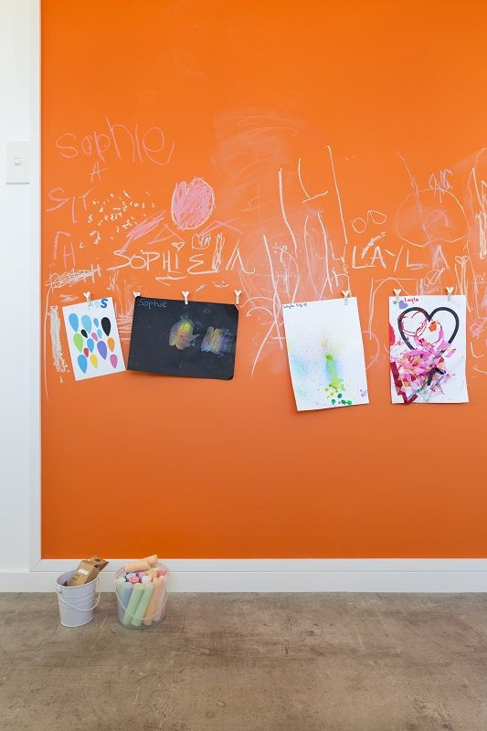 Funky orange chalk-board at handy 'kid-height' in the kitchen, teams with a cool concrete look vinyl on the floor. Decorating products are available in New Zealand through Guthrie Bowron stores.