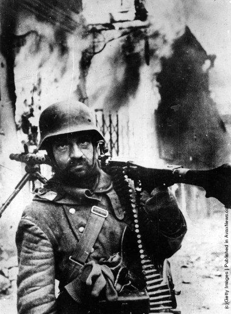 A dejected German Grenadier carrying a machine gun on his shoulder in front of a building on fire during the German retreat in Russia. (Photo by Keystone/Getty Images). 1944