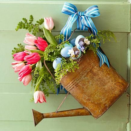 Rustic appeal - Repurpose a vintage watering can into a spring oasis. Set floral foam in the can to secure stems. Blown eggs and ferns create a tiny garden with multi-hued pink tulips as a background bouquet.