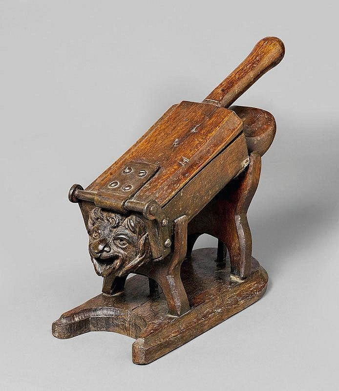 A FRUIT AND GRAIN PRESS, France, 19th c. Carved oak in the shape of a lion's head. L 45, H 37 cm.