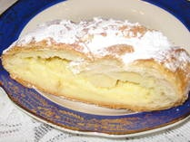 Cheese strudel, made with Farmer's cheese sweetened with honey, wrapped in phyllo dough and sprinkled with powdered sugar.