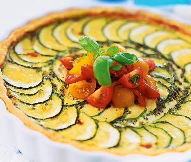 Charmerande paj med en välsmakande fyllning av mozzarellaost, pesto och zucchini. Ett utmärkt vegetariskt alternativ till en festmåltid eller att servera på buffébordet. Toppa med körsbärstomater och basilika i balsamvinäger.