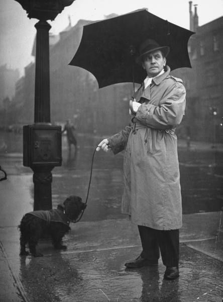 Actor Fredric March with his cocker spaniel on the street on a rainy day. (April 1944)