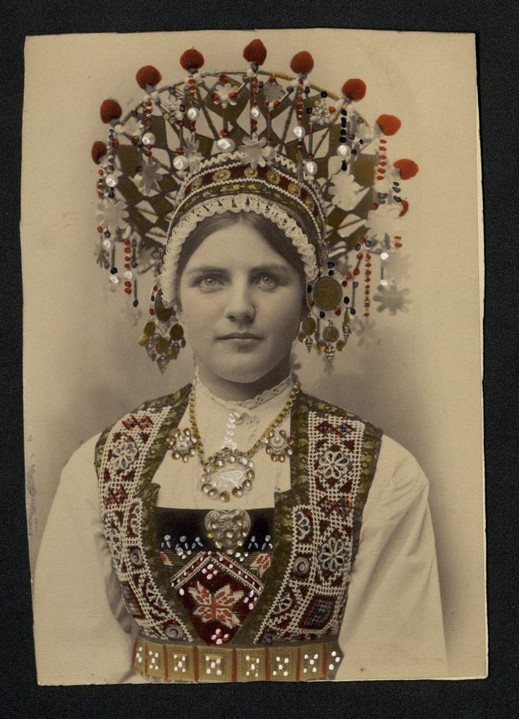 Norwegian bride wearing a traditional folk costume with a bridal crown. You will notice the bridal crown has small metal discs and beads hanging from it which produce a melodic tinkling and according to some legends this is supposed to ward off evil spirits from the bride.