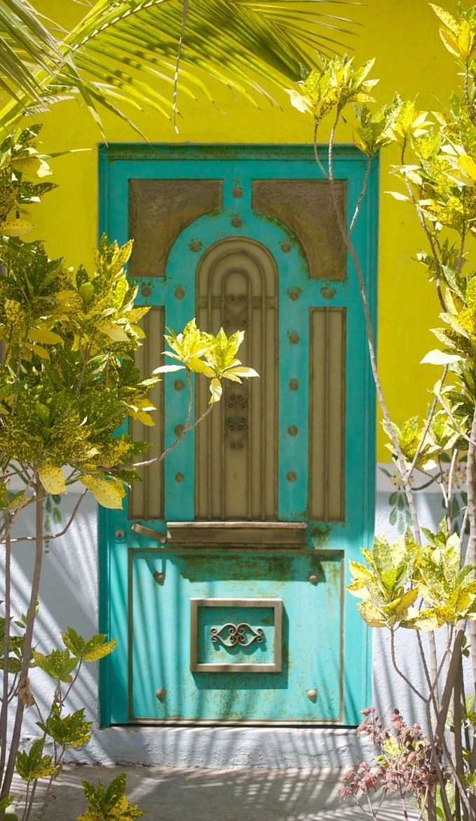 a beautiful brass trimmed antique door in a yellow wall with tropical trees and lovely hand painted panels on the wall in Melaque, Mexico