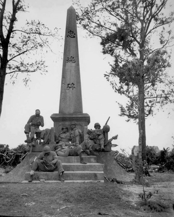 American US Marines and sailors resting at the base of a Japanese war memorial Okinawa Japan 12 April 1945.