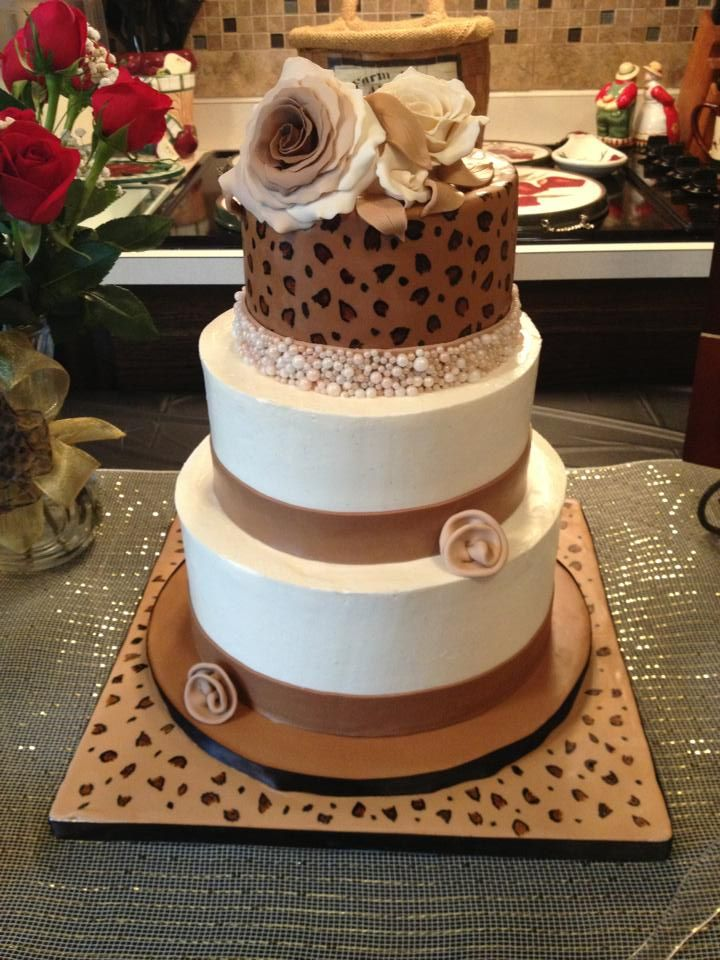 Leopard Print Bridal Shower - The bottom two tiers are covered in IMBC with fondant ribbon and fondant ribbon roses.  The top tier is covered with MMF hand painted leopard print, gumpaste roses and fondant band with non-coated sugar pearls that I coated with copper and pearl luster dust.  Attached them using piping gel (that was challenging and time consuming....and messy! Sugar pearls falling everywhere!) The cake boards are covered in MMF and hand painted.