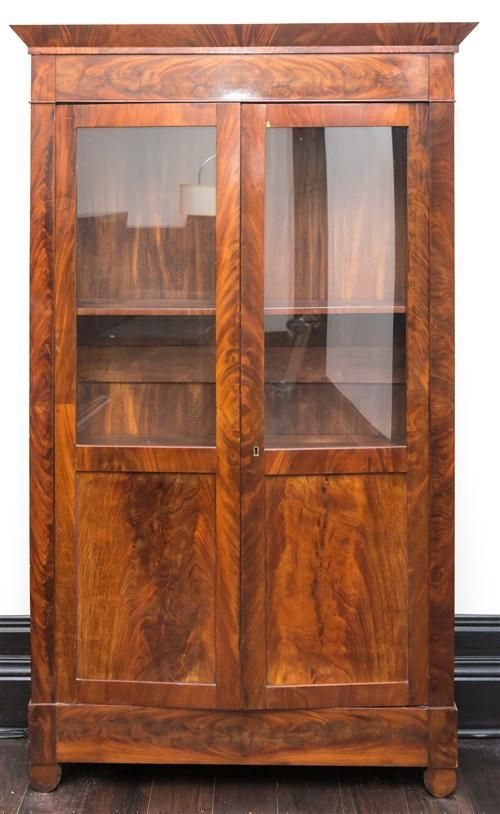 A walnut mahogany veneered two door bookcase, with glass doors and shelved interior, H 216, W 130, D 38cm Film Provenance; Austral...