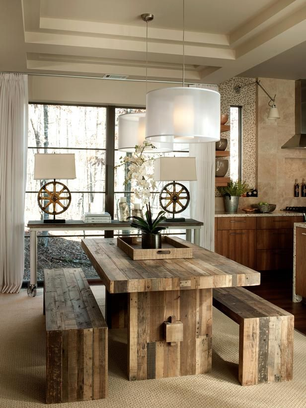 Rustic Chic: Running along an axis that connects the kitchen and great room to outdoor spaces, the dining room is positioned to take advantage of dramatic views. Anchored by a sisal-style rug, the space showcases rustic-chic furnishings and a console table fashioned from reclaimed material. The table and benches were created from old wood pallets. From HGTVRemodels.com