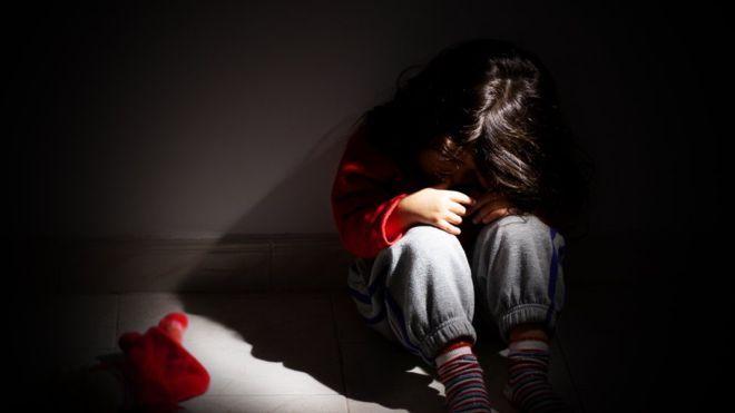 """La niña mostraba """"varios moretones profundos en el trasero, espalda baja y piernas; hinchazón en la mejilla derecha; una magulladura en la frente; lesiones en proceso de curación en toda la espalda y sangre seca en la esquina de la boca"""". También tenía """"marcas de ligaduras sobre las muñecas que indican que había sido sujetada y parecía estar malnutrida"""". Según el informe de la policía, cuando se le preguntó a la niña cómo se llamaba, ella respondió """"idiota""""."""