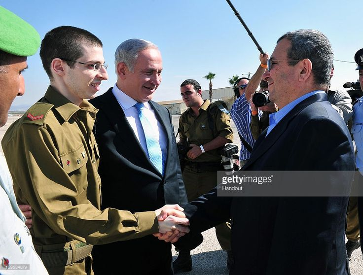 In this handout photo provided by the Israeli Defence Force, freed Israeli soldier Gilad Shalit (L) shakes hands with Defence Minister Ehud Barak (R) next to Israeli Prime Minister Benjamin Netanyahu (C) at Tel Nof Airbase on October 18, 2011 in central Israel. Shalit was freed after being held captive for five years in Gaza by Hamas militants, in a deal which saw Israel releasing more than 1,000 Palestinian prisoners.