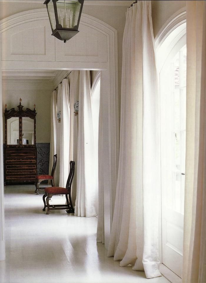 """ ... the utterly simple curtains are made from 200 yards of pure white medium-weight Italian linen with a matte satin finish, hung with a glamorous drape from plain wrought iron rods."""