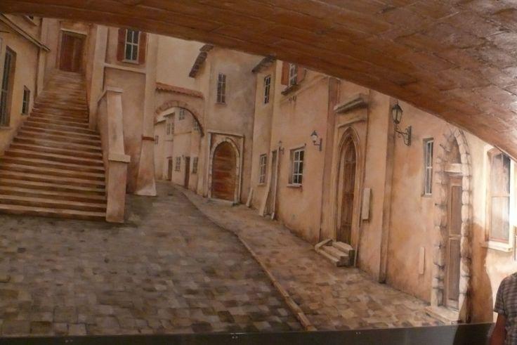 Wall painting, artystyczne malowanie ściany farbami akrylowymi, praca przedstawia uliczkę w perspektywie. Mural ścienny wykonany w gabinecie architekta. Kolorystyka malowidła w sepii.