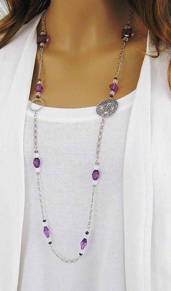 Long purple beaded necklace with purple, and clear beads, with large silver filigree connector, and silver hoop.
