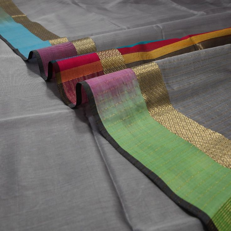 #PadmaPaaduka #Handwoven Light Grey Silk Cotton Sari with Multi-Coloured Border ~ A beautiful amalgamation of sombre grey and vibrant colours defines this silk cotton sari; a handwoven creation from Padma Paaduka. A two-tone grey dominates the body while the colourful border is highlighted with a zari band. Thin multi-coloured stripes are seen on either ends of the grey pallu. A lovely rani pink blouse offers a vivacious contrast. Code 820512397
