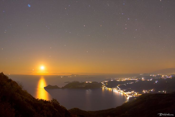 Chelidonofolia nightscape view - Chelidonofolia nightscape view  Night landscape view from Kratsalo mountain of Corfu, with the setting Moon above Agios Georgios beach of north.  With souther leg of Italy just under the Moon and the moonlight fading through Porto Timone peninsula. On the top right we can see the sitting in the heavens tied to a chair, Queen Cassiopeia. While on the top left are the seven sisters of Atlas and Pleione.