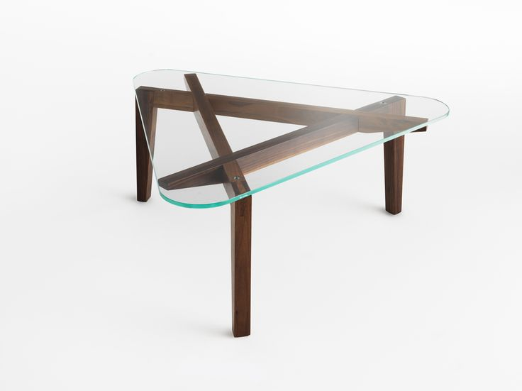 "Autoreggente / Design: Patrizia Bertolini, 2016.  ""Ponty"" inspired table and coffee table characterised by the interlocking of legs which guarantees a balance of forces capable of acquiring three-dimensional shape without the use of screws or glue. A static system which consists of three identical ""L"" elements that create a grid which, combined with the round shapes of the base, generates a visually dynamic rotation effect. The top is made of tempered glass to give the product a light…"