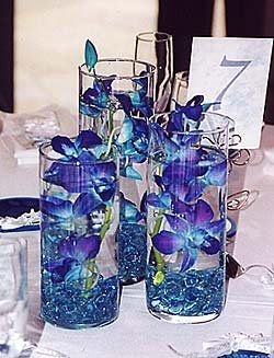 love this idea with the blue gem rocks on the bottom - Dollar tree has the small cylinder vases. could line those down the middle of the table rather than cluster? Add a light to the bottom?