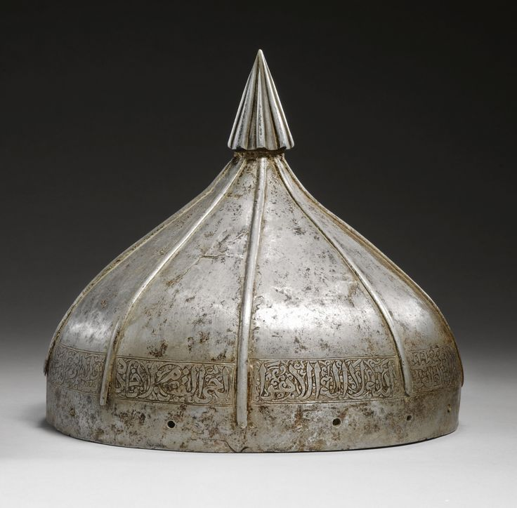 A LATE ILKHANID OR EARLY TIMURID STEEL HELMET, PERSIA, 14TH CENTURY of domical form of ogee section applied with eight slender filaments running vertically, around the base the interstice between each filament chased with a cartouche of cursive calligraphy on foliate scrolls, a series of pierced holes, some retaining portions of pins, around the base, a later finial of pointed form with eight tapering ribs