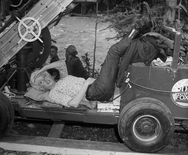 Marilyn Monroe finds a comfortable spot to take a rest during location filming of River of No Return at Jasper National Park, Canada