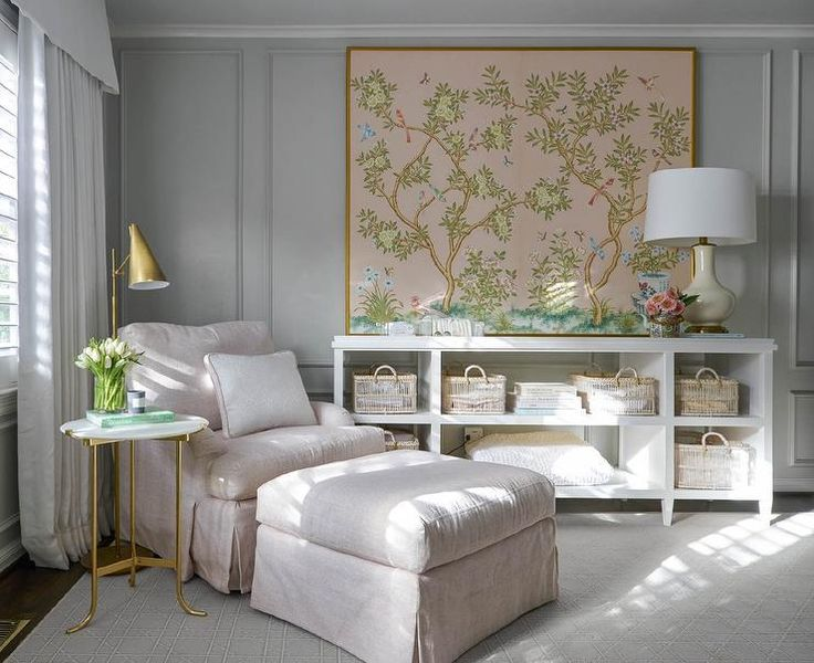 Elegant pink and gray nursery boasts gray walls accented with gray trim moldings and framed pink chinoiserie fabric art piece mounted above a white shelving unit.
