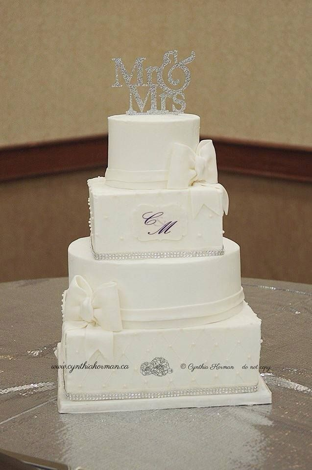Alternating round and Square wedding Cake.   Classic white with fondant bows.